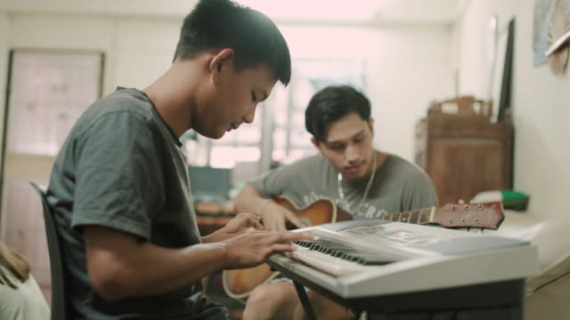 asian man playing his guitar on the house with friends stock video - piano key stock videos & royalty-free footage