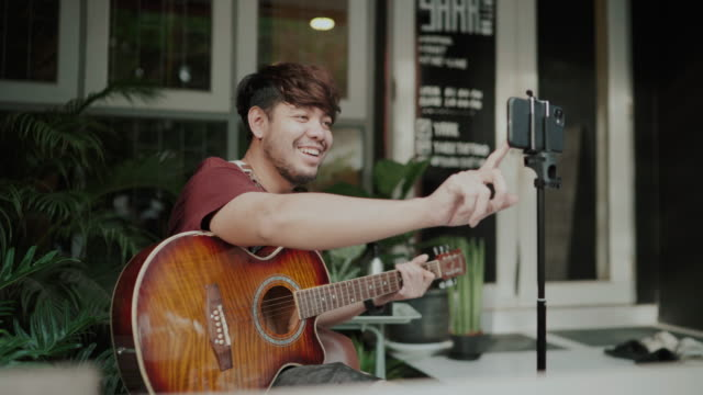 asian man playing music together through a video call on the internet - hobbies stock videos & royalty-free footage