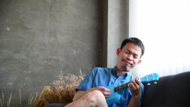 vídeos de stock, filmes e b-roll de homem asiático que joga o ukulele e o instrumento da música - ukulele