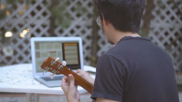 vídeos de stock, filmes e b-roll de homem asiático jogando ukulele enquanto assiste laptop - ukulele