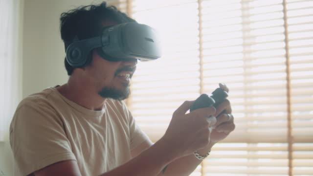 vídeos de stock, filmes e b-roll de homem asiático jogando videogame com vr em casa - controle