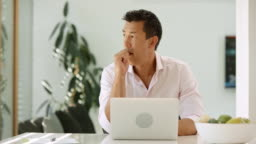 DS Asian man pondering while working on his laptop