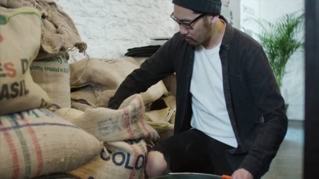 asian man pours coffee beans - bag stock videos & royalty-free footage