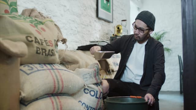 asian man pours raw coffee beans to the bucket (slow motion) - barista stock videos and b-roll footage