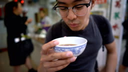 Asian Man Presenting and Tasting Famous Chinese Herbal Tea in front of the Camera
