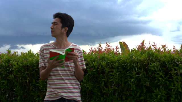 asian man reading a book, flipping a book at outdoor - only mid adult men stock videos & royalty-free footage
