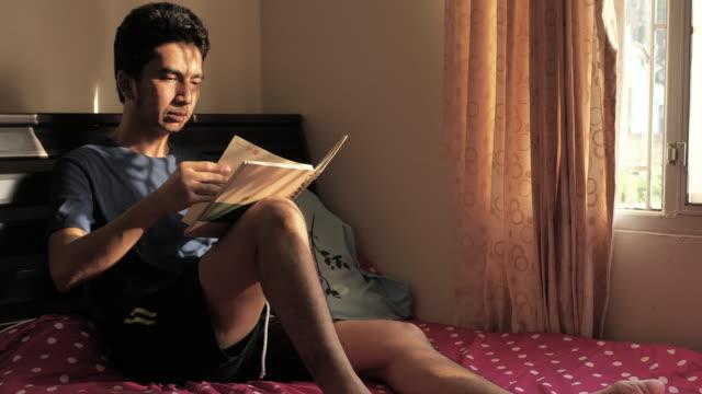 昼間の窓の近くで、窓から日光で本を読むアジア人男性 - 30代点の映像素材/bロール