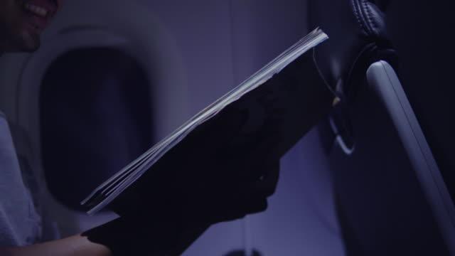 asiatischer mann liest reisebuch im flugzeug - flugpassagier stock-videos und b-roll-filmmaterial