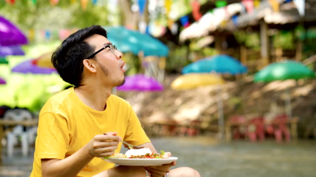 asian man relaxing eating pad kra pao, one of the most popular thai food, rice with basil spicy pork - thai culture stock videos & royalty-free footage