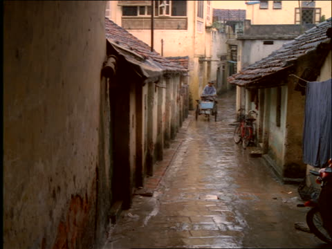 Asian man riding pedicab in alley in rain / Vietnam