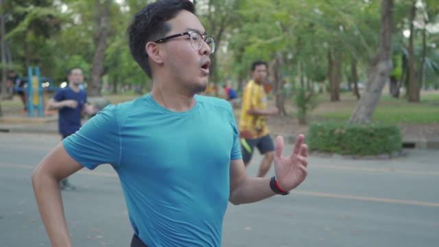 slo mo - アジアの男が走り、公共の公園で人々を取る(サイドビュー) - 陸上選手点の映像素材/bロール