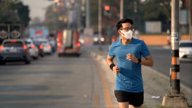 slo mo asian man running in city traffic intersection  with air pollution mask in chiang mai, thailand - air pollution stock videos & royalty-free footage