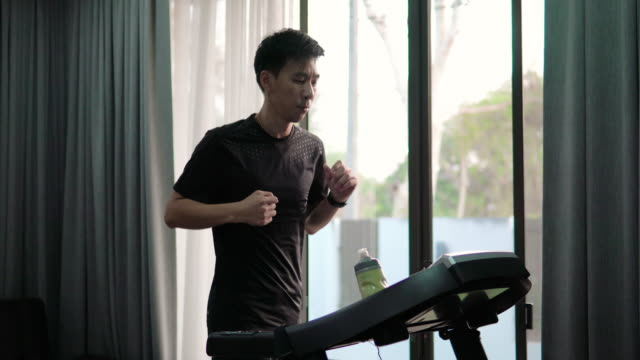 asian man running on treadmill at home. - treadmill stock videos & royalty-free footage