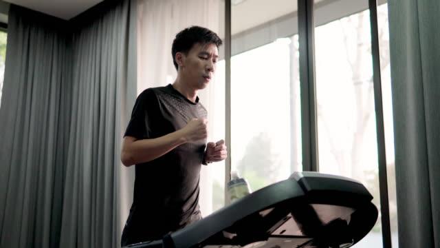 asian man running on treadmill at home. - treadmill stock videos & royalty-free footage
