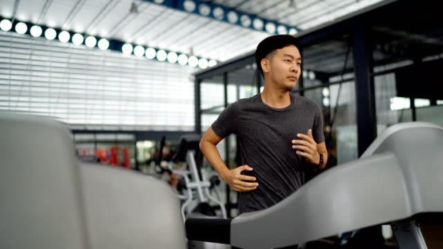 asian man running on treadmill - treadmill stock videos & royalty-free footage