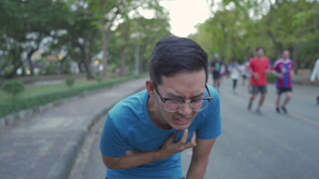asian man running too fast before stop to catching his breath and holing his heart - heart attack stock videos & royalty-free footage