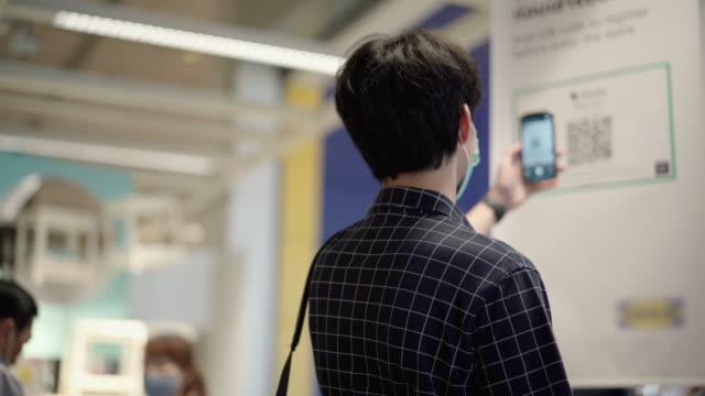 vidéos et rushes de l'homme asiatique scannent le code qr avant d'aller faire du shopping - équipement