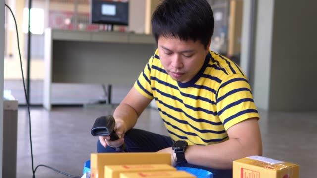 stockvideo's en b-roll-footage met aziatische man scannen pakketten met een handheld barcode scanner. - productielijn werker