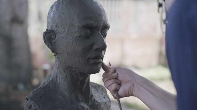 asian man sculptor creates a clay sculpture. - carving craft product stock videos & royalty-free footage