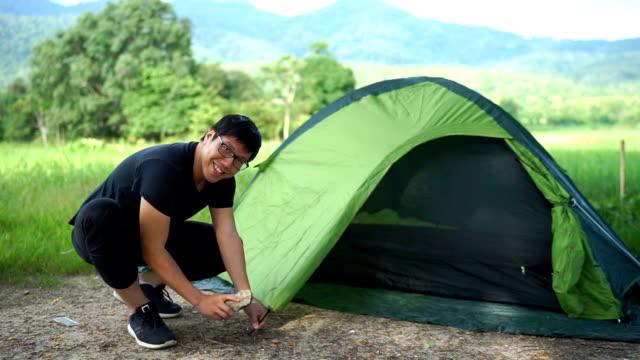 stockvideo's en b-roll-footage met aziatische man instelling tent op vakantie buiten met mountain achtergrond - tent