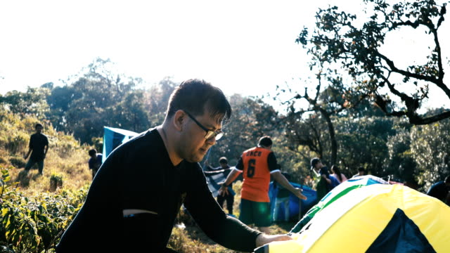 asian man setting up camping tent place in birch woods forest