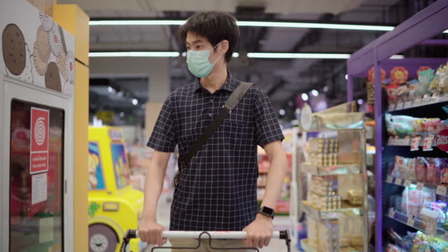 asian man shopping in supermarket with face mask protection - east asian ethnicity stock videos & royalty-free footage