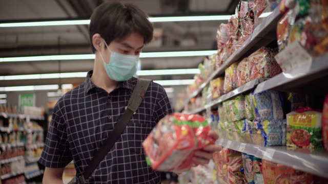 asian man shopping in supermarket with face mask protection - price stock videos & royalty-free footage