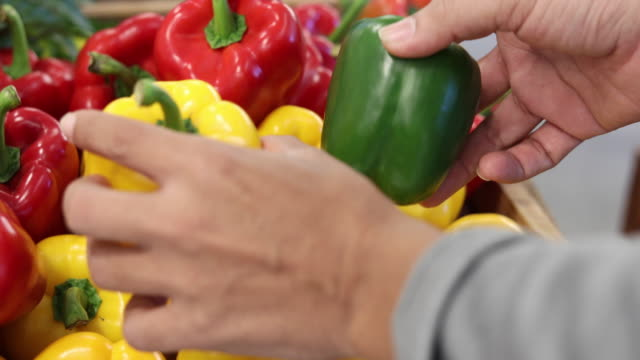 asian man shopping red and yellow bell peppers in supermarket - red bell pepper stock videos & royalty-free footage