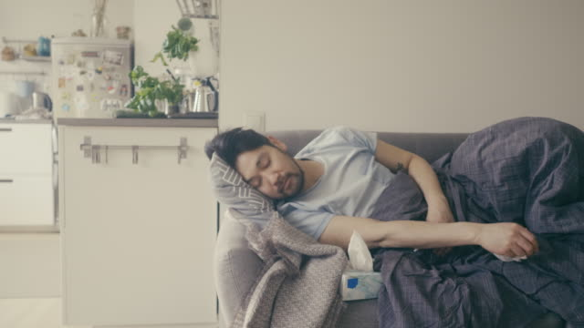 asian man sick at home with cold and sleeping on a sofa - sofa stock videos & royalty-free footage