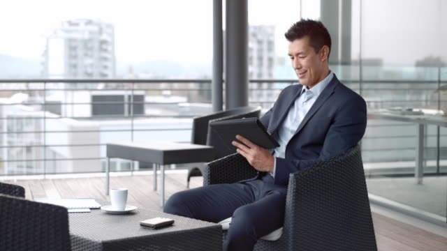 asian man sitting in the terrace lounge of a business building in and working on the digital tablet - businesswear stock videos & royalty-free footage
