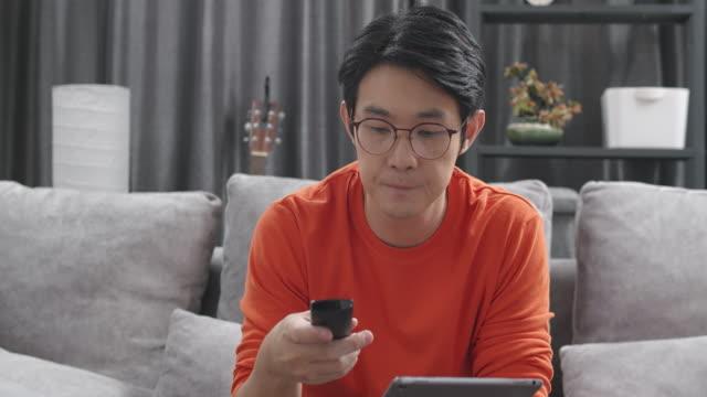 asian man sitzt auf einer couch und schaut fernsehen und tippt oder sucht auf seinem tablet zu hause während coronavirus quarantäne lockdown situation. erwachsene, die multitasking durch wechseln des kanals durch die verwendung von fernbedienung und übe - suchen stock-videos und b-roll-filmmaterial