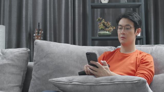 asian man sitzt auf einer couch und schaut fernsehen und tippt oder sucht auf seinem smartphone zu hause, während coronavirus quarantäne-sperrsituation. erwachsene, die multitasking durch wechseln des kanals durch die verwendung von fernbedienung und üb - fade in video transition stock-videos und b-roll-filmmaterial