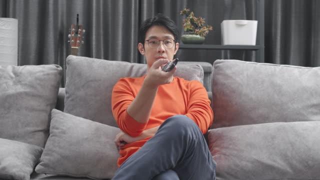 asian man sitzt auf einer couch und schaut zu hause im wohnzimmer fernsehen, während das coronavirus quarantäne-sperrsituation. erwachsenen-wechselkanal mit fernbedienung. - fade in video transition stock-videos und b-roll-filmmaterial