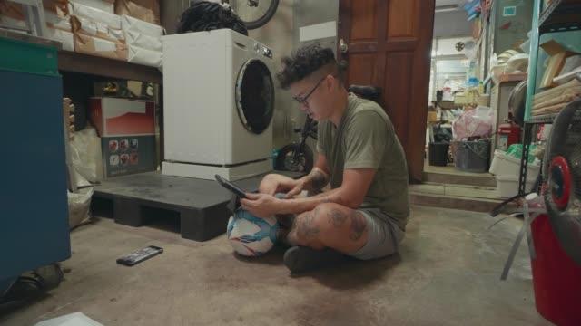 asiatische mann sitzt auf dem boden in der waschküche mit tablet zu arbeiten. - cool und lässig stock-videos und b-roll-filmmaterial