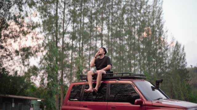 asian man sitting on the roof of the car and drink coffee - hippy stock videos & royalty-free footage