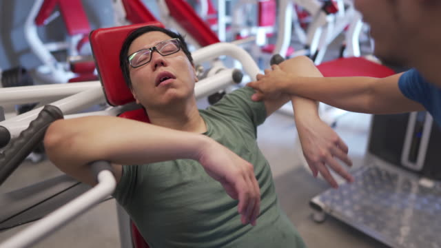 asian man sleeping in gym while doing workout routines before his friend wakes him up, comedian concept - mouth open stock videos & royalty-free footage