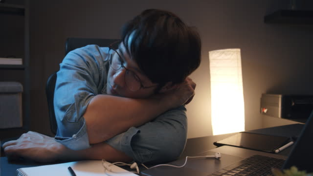 asian man sleeping in home office with overworked. he feel tried from work and napping while working at home in the night time. sleeping on duty - napping video stock e b–roll