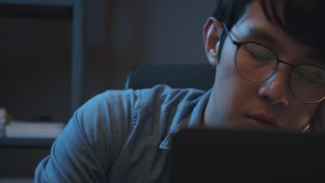 過労でホームオフィスで眠っているアジア人男性。彼は夜の時間に家で仕事をしながら仕事や昼寝から試みられたと感じています。勤務中に寝る - 怠惰点の映像素材/bロール