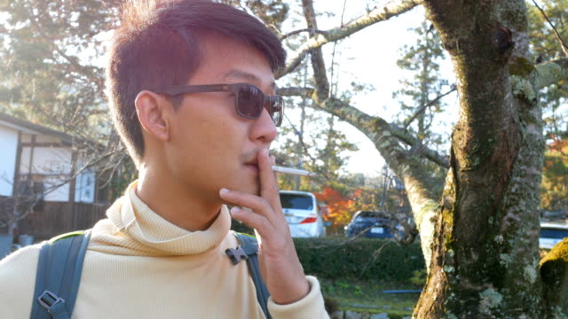 asian man smoking cigarette in winter - smoking issues stock videos & royalty-free footage