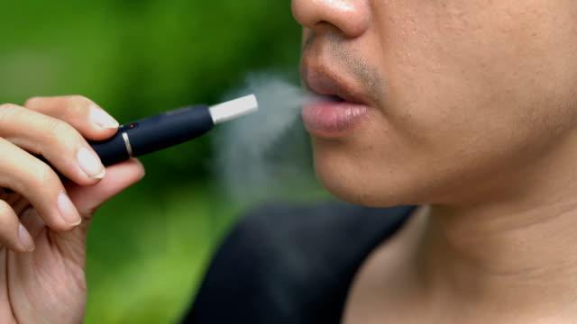 cu asian man smoking iqos - tobacco crop stock videos & royalty-free footage