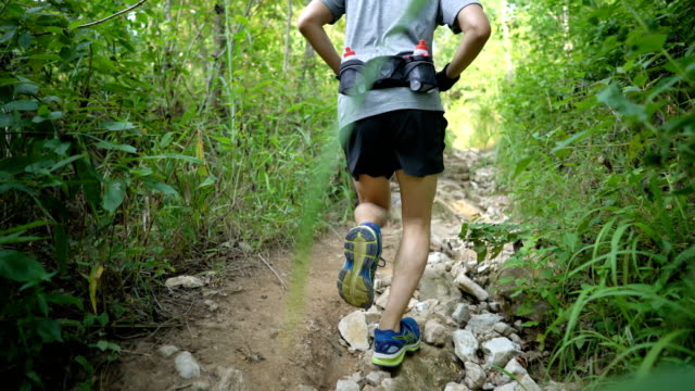 cu ts la asian man sprinting in rocky trail path - at the edge of stock videos and b-roll footage