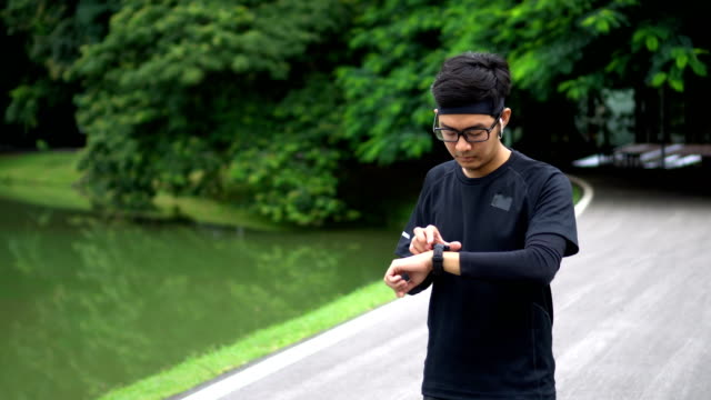 asian man starts jogging using his heart rate sport watch in nature park - mack2happy stock videos and b-roll footage