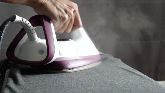vídeos y material grabado en eventos de stock de hombre asiático tela de planchado al vapor en casa. papel de una mujer deber. ropa doméstica y concepto de hogar. - plancha