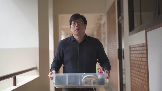 asian man stops to wipe sweat while carrying a box and walking for moving or moving office concept - moving office stock videos & royalty-free footage