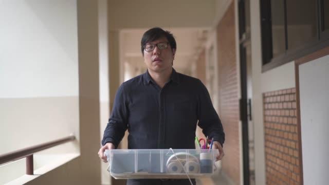 vidéos et rushes de l'homme asiatique s'arrête pour essuyer la sueur tout en portant une boîte et marchant pour déplacer ou déplacer le concept de bureau - employée