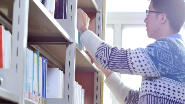 asian man student searching book in library - library stock videos & royalty-free footage