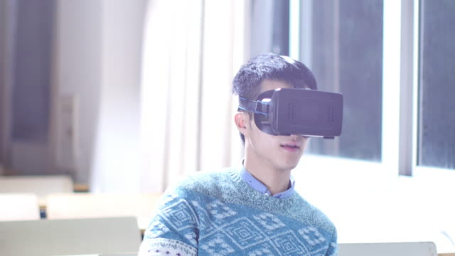 asian man student using VR near window