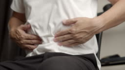 Asian man Suffering from stomachache at home.healthcare and medical concept.