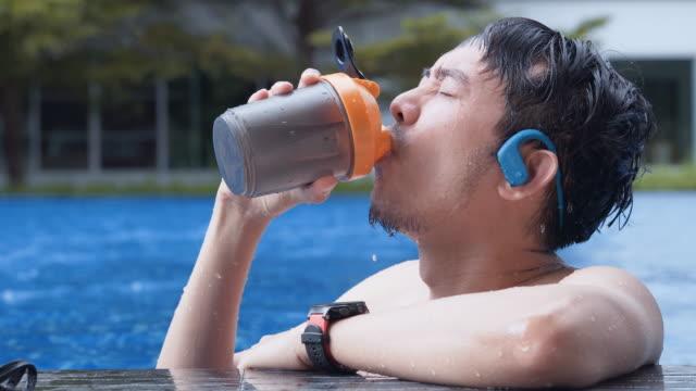アジアの男はプールの端に泳ぐ、一口を取り、続ける - プールサイド点の映像素材/bロール