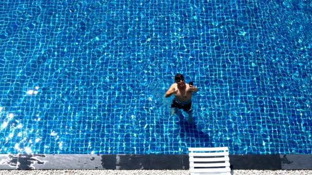 asian man swimming then take a selfie from his moblie phone - swimming shorts stock videos & royalty-free footage